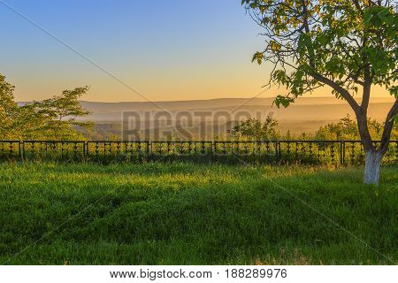 On a forward background a dark grass, on the second plan the small fencing behind which is looked through a landscape with the wood and a height which are lit up by beams of the morning Sun.
