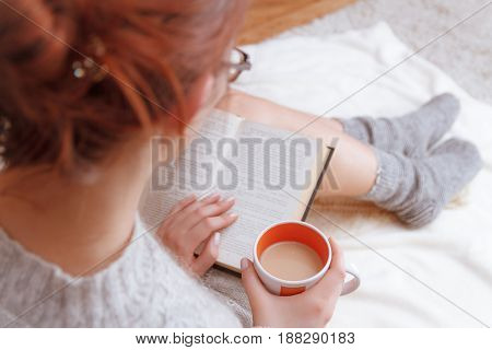 Soft photo of a woman in a cozy sweater on the bed with the old book and a cup of tea with milk in their hands