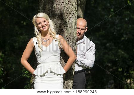Smiling couple in park. Young people resting in nature. Man and woman leaned against a tree natural environment background