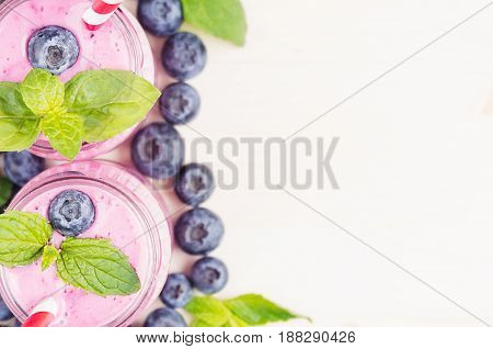 Decorative border of violet blueberry fruit smoothie in glass jars with straw mint leaves berries close up top view. White wooden board background copy space.