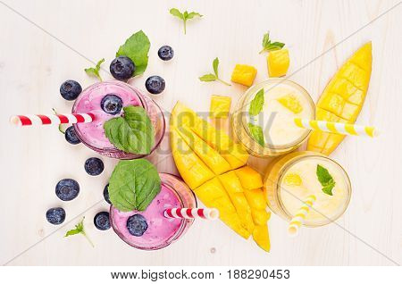 Yellow and violet fruit smoothie in glass jars with straw mint leaves mango slices berry top view. Soft white wooden board background.