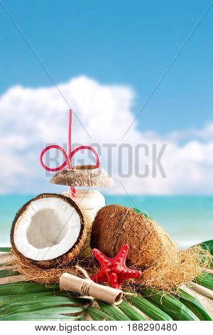 Marine composition of coconut and palm leaves on the background of beautiful sea landscape. Suitable as a card.