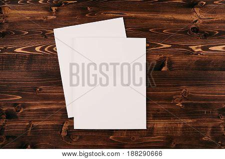 Blank white paper A4 envelope on vintage brown wooden board. Mock up for branding identity.