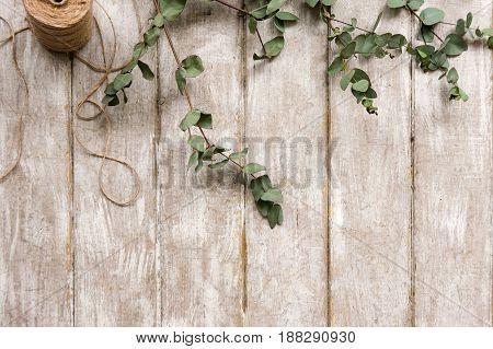 Laurel decor on wood background top view. Floristry workshop table. Decorative artwork from spring flower