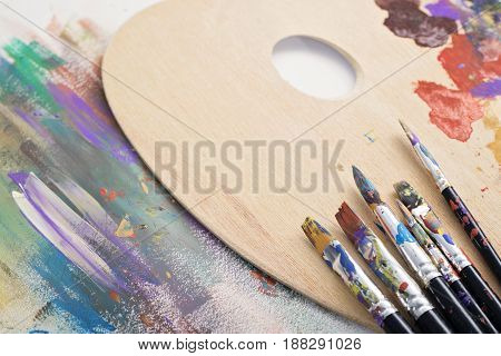 Paint brushes, palette and artwork on white canvas