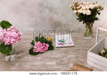 Workplace with flowers, bouquet and sketch. Floristry workshop wooden table with decor. Decorative artwork from spring flower