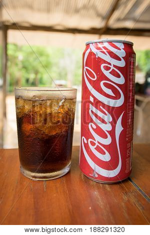 PAI THAILAND 23 MAY 2017: Coca-Cola can drink and a glass of coke with ice cubes over wooden table in Pai Thailand