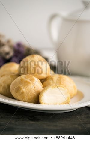 Homemade cream puffs filled with vanilla custard cream on white plate put on rustic wood table serve with tea in white pot or cup of coffee. Cream puffs or choux cream or eclairs.