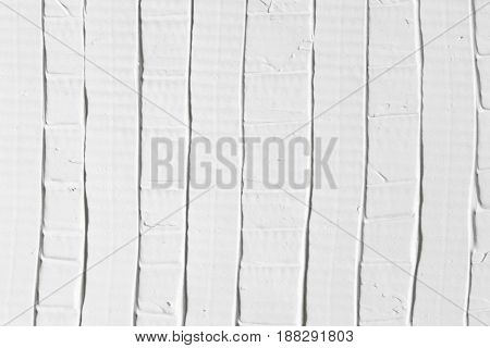 Relief white surface with vertical stripes, plaster texture. Stucco abstract background with free space. Handmade pattern, decorative design, diy concept