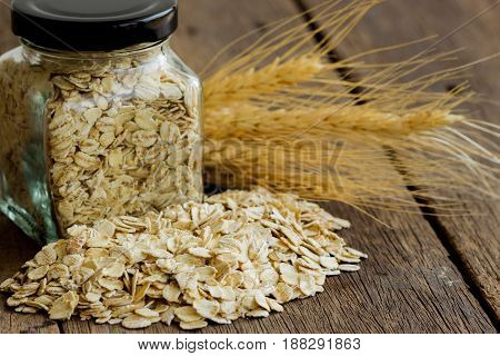 Oat flakes or oatmeal in glass bottle on rustic wood table. Rolled oat is clean food for health. Prepare oat flakes for bakery or cooking. Natural organic food in vintage style concept.