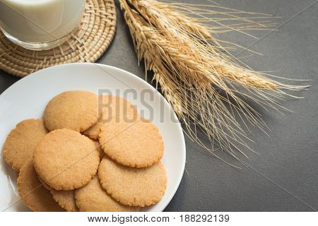 Thin biscuits or cookies on white plate serve with fresh milk on granite table. Homemade thin biscuits cookies for meal. Crispy biscuits cookies so delicious.
