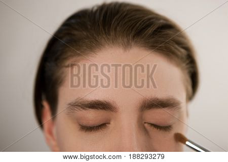 Applying concealer to cover dark circles under the eyes. Horizontal indoors close-up shot of man with eyes closed and brush for makeup. Male beauty , gender equality concept.