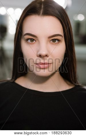 Young woman with natural makeup looking at camera. Without contouring phase of make-up