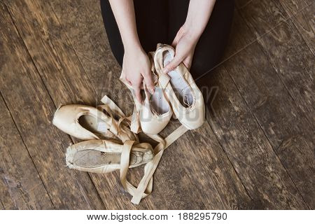 Ballerina holding ballet shoes in hands. Ballet shoes are near. Top view photo. Horizontal. close-up.