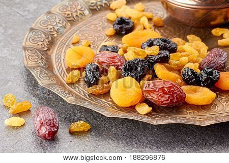 Various dried fruits on toreutic plate over stone background. East style