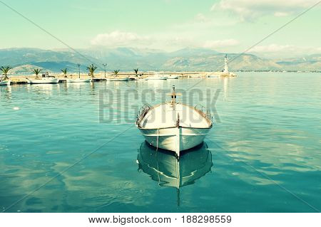 Small fishing boat in small marina. A small fishing boat in small marina. A tranquil and peaceful background with calming effect. A small Greek fishing harbour with a few boats in the background.