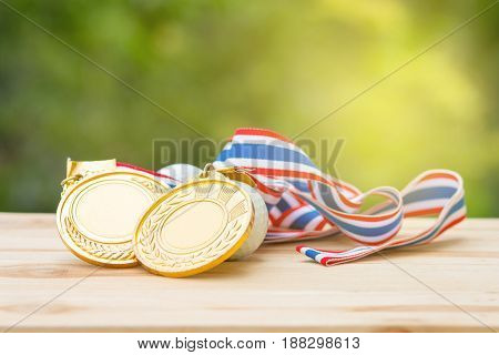 two old gold medal and golf ball on wood in morning soft background Winner concept