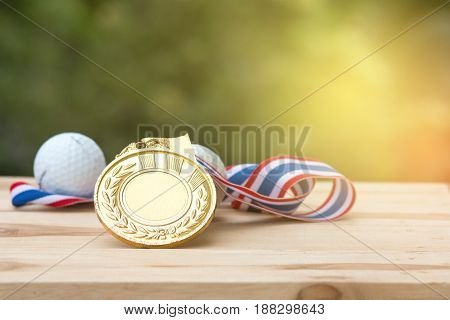 old gold medal and golf ball on wood in morning soft background Winner concept