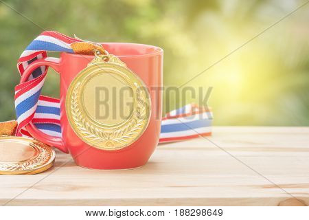 gold medal and red cup coffee on wood in morning soft background Winer concept
