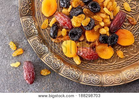 Various dried fruits on toreutic plate over stone background. East style, top view