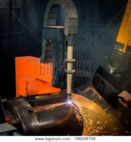 Industrial plasma laser cutting torch cuts steel tubes with preprogrammed patterns
