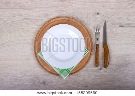 Empty Plate, Fork And Knife On Wooden Background.