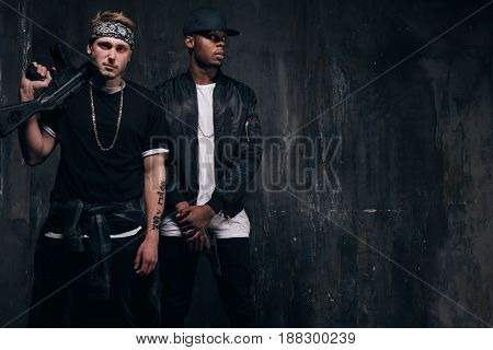 Group of young criminals with guns. Armed band of gangsters with tattoo and weapon on dark background. Outlaw, ghetto, murderer, robbery concept