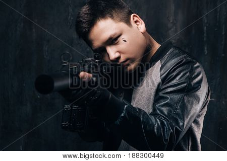 Tattooed killer shoots a sniper rifle close-up. Armed white gangster man with weapon and tattoo on dark background. Outlaw, ghetto, murderer, robbery concept