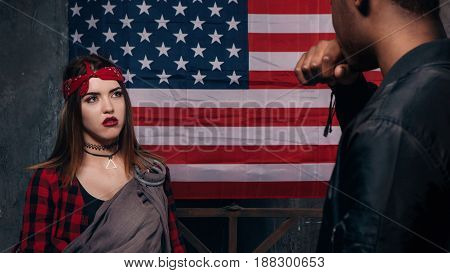 Quarrel in american family. Black man and caucasian woman with little baby on US national flag background. Social problem, child custody, youth pregnancy concept