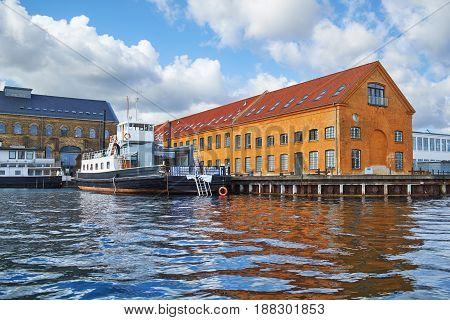 The Moored Ship Near Quaysidenear With Red Roof House In Copenhagen, Denmark.