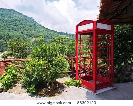 Red telephone booth against mountain and tree background