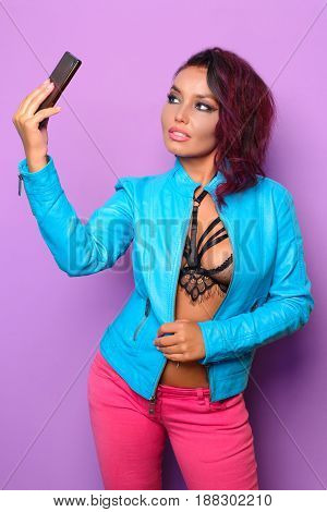Fashion pretty woman makes self portrait on smartphone in blue jacket over purple background.