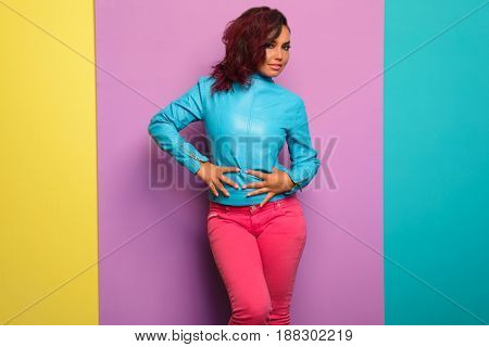fashion model in blue leather jacket denim pants. Posing over Tricolor background.