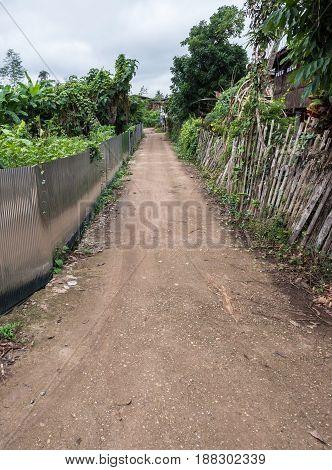 Small concrete road which between the wooden fence and zinc fence to the countryside village in Thailand.