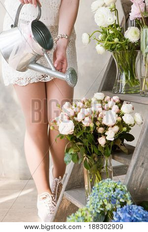Woman watering bouquets of fresh flowers of fresh flowers. Slim florist work in flower shop with fresh bouquets. Beautiful decor for wedding