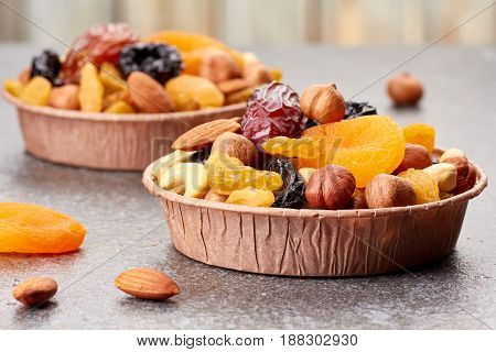 Two paper forms with mix of dried fruits and nuts over stone background