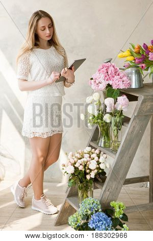 Florist inspects a range of flowers. Business woman with tablet in flower shop. Small business management, female manager, time management, online flower sales concept
