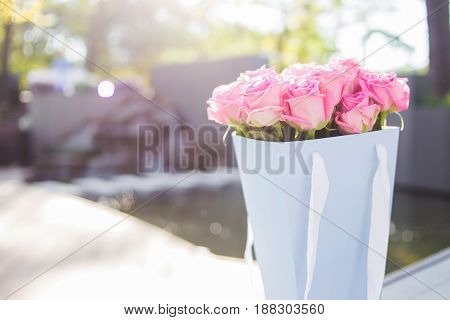 bouquet with pink fresh roses in blue paper bag