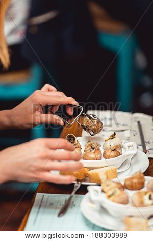 Woman going to eat Snails with herbs butter, in traditional ceramic pan with cut parsley, bread and and parsley sauce on textile napkin over rustic wooden table. restaurant food and wine tasting