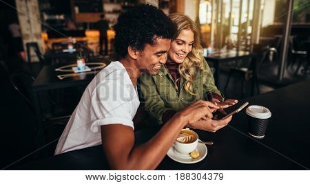 Shot of happy young man with his female friend sitting together at cafe and using mobile phone. Best friends at coffee shop looking at smart phone.