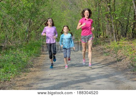 Family fitness and sport, happy active mother and kids jogging outdoors, running in forest