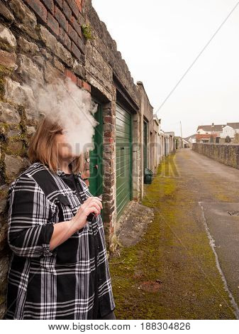A mature woman smokes an electronic cigarette outside in poor weather conditions
