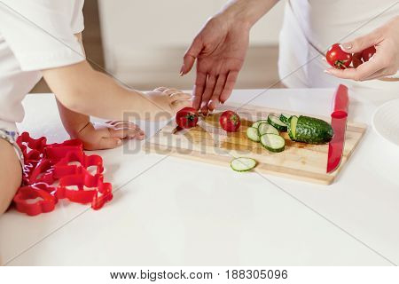Close up shot of hands cutting cucumber and tomatoe. Chil's hands with mother hands.