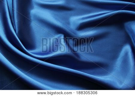 Blue shiny fabric folds. Fancy festive fabric. Abstract textile background