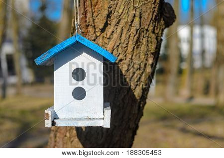 White birdhouse with blue roof on tree in the garden