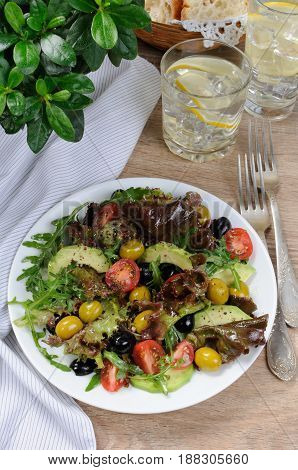 Summer salad - with avocado olives tomatoes in lettuce dressed mustard-garlic sauce
