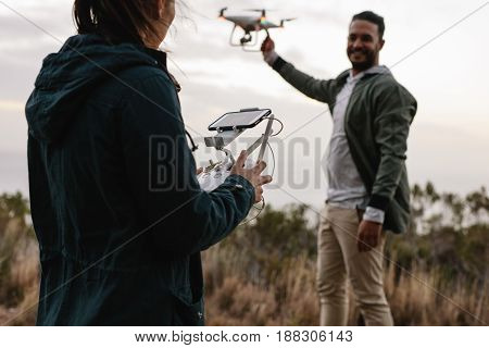 Young Couple Flying Drone In Countryside