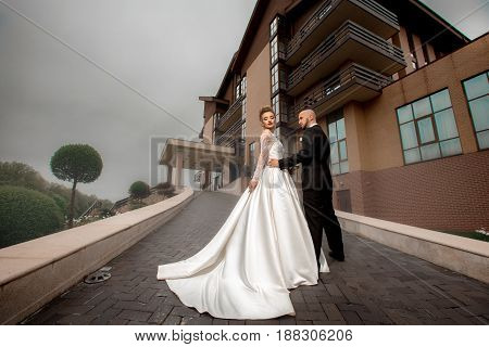 glamrou young merried couple posing outdoors at raining weather
