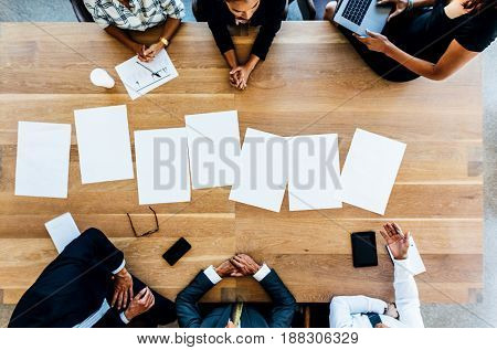 Blank Placards On Table With Business People Sitting Around