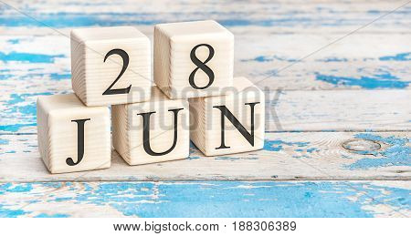 June 28th. Wooden cubes with date of 28 June on old blue wooden background.